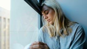Потревоженная женщина сидя около окна 4k видеоматериал