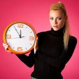 Потревоженная женщина с большими оранжевыми часами показывать задержка, спешка, nervo стоковые изображения rf