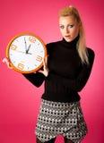 Потревоженная женщина с большими оранжевыми часами показывать задержка, спешка, nervo стоковые фото