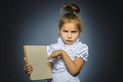 Потревоженная или усиленная девушка с книгой ребенок на серой предпосылке концепция исследований стоковое изображение rf