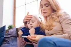Потревоженная мать касаясь ее лбу childs Стоковые Изображения