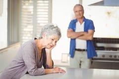 Потревоженная старшая женщина сидя при человек стоя в предпосылке Стоковые Изображения RF