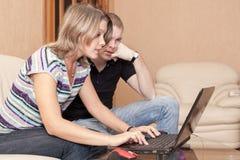 Потревоженное кавказское сообщение печатания человека и женщины и смотреть экран компьтер-книжки, эмоции во время играть игры или стоковое изображение