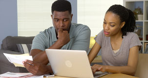 Потревоженные Афро-американские пары смотря через счеты онлайн стоковое изображение rf