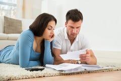 Потревоженные молодые пары высчитывая их счеты дома Стоковые Изображения RF