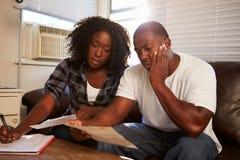 Потревоженные молодые пары сидя на софе смотря счеты стоковые фотографии rf
