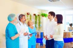 Потревоженные родственники слушают к медицинскому персоналу о новостях от трудной хирургии после злоключенья стоковая фотография