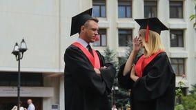 Потревоженные студент-выпускники в академичных платьях говоря о жизни после градации видеоматериал