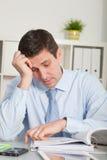 Потревоженный бизнесмен анализируя служебные документы Стоковое Фото
