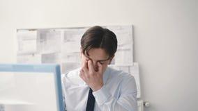 Потревоженный бизнесмен работает с компьютером в офисе 4K акции видеоматериалы