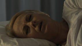 Потревоженный зрелый женский спать в ее плохом, страдающ от сердечной боли, конец-вверх акции видеоматериалы