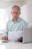 Потревоженный зрелый человек с финансами домочадца компьтер-книжки расчетливыми Стоковые Фото