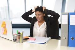 Потревоженный и отчаянныйся стресс страдания коммерсантки работая на столе компьютера офиса Стоковая Фотография