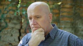 Потревоженный и побеспокоенный бизнесмен выглядя расстроенный и разочарованный стоковое изображение