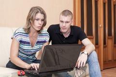 Потревоженный молодой кавказец поженился сообщение чтения пар на экране компьтер-книжки в отечественной комнате стоковые фото