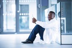 Потревоженный доктор сидя на поле с цифровой таблеткой Стоковые Изображения