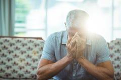 Потревоженный старший человек сидя в живущей комнате Стоковые Фото