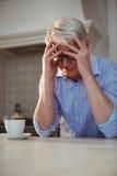 Потревоженный старший человек сидя с чашкой кофе Стоковая Фотография RF