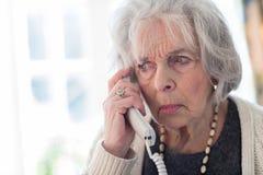 Потревоженный телефон старшей женщины отвечая дома стоковая фотография rf