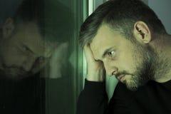 Потревоженный человек смотря через окно Стоковое Изображение