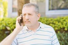 Потревоженный человек среднего возраста говоря на телефоне Стоковые Фото