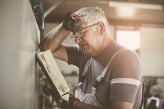 Потревоженный человек читая его плановика Стоковое Изображение