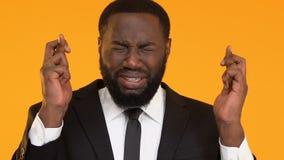Потревоженный чернокожий человек в пальцах костюма пересекая для удачи перед собеседованием для приема на работу акции видеоматериалы