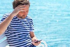 Потревоженный человек в striped рубашке матроса читая передвижное сообщение SMS Стоковая Фотография RF