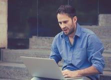 Потревоженный человек работая на портативном компьютере сидя outdoors Стоковое Фото