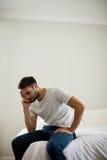 Потревоженный человек сидя в спальне Стоковая Фотография