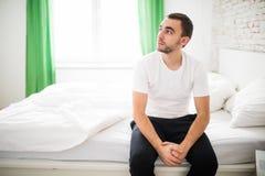 Потревоженный человек сидя на кровати с рукой на лбе дома Стоковое фото RF