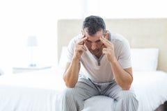 Потревоженный человек сидя на кровати Стоковое Изображение