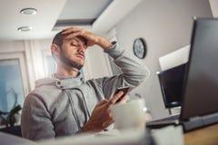 Потревоженный человек смотря умный телефон Стоковая Фотография RF