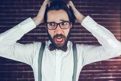 Потревоженный человек с головой в руках смотря прочь Стоковое фото RF