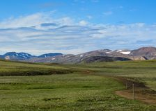 Потрясающий вид зеленой зоны Hvanngil и красочных гор риолита Tindafjoll со снегом на предпосылке в солнечном дне с синью стоковое изображение