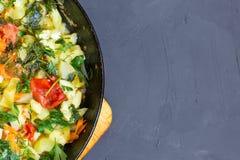 Потушенное вегетарианское тушёное мясо от vegetable сердцевины, томатов, перца, укропа и петрушки в сковороде на темной предпосыл Стоковое Изображение