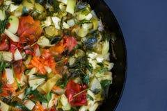 Потушенное вегетарианское тушёное мясо от vegetable сердцевины, томатов, перца, укропа и петрушки в сковороде на темной предпосыл Стоковое Изображение RF