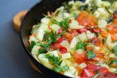 Потушенное вегетарианское тушёное мясо от vegetable сердцевины, томатов, перца, укропа и петрушки в сковороде на темной предпосыл Стоковые Изображения RF