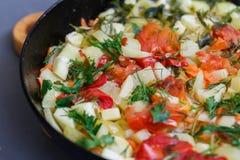 Потушенное вегетарианское тушёное мясо от vegetable сердцевины, томатов, перца, укропа и петрушки в сковороде на темной предпосыл Стоковое фото RF