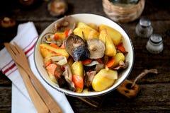 Потушенные картошки с луком, грибами, морковью, розмариновым маслом и чесноком в оливковом масле Стоковая Фотография
