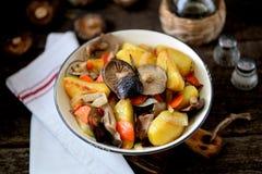 Потушенные картошки с луком, грибами, морковью, розмариновым маслом и чесноком в оливковом масле Стоковое фото RF