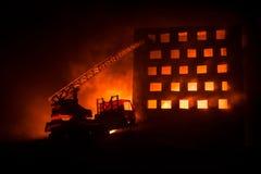 Потушите огонь частного дома на ноче Забавляйтесь пожарная машина с длинной лестницей и горящее здание на ноче Концепция пожарной стоковое фото rf
