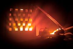 Потушите огонь частного дома на ноче Забавляйтесь пожарная машина с длинной лестницей и горящее здание на ноче Концепция пожарной стоковое изображение rf