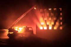 Потушите огонь частного дома на ноче Забавляйтесь пожарная машина с длинной лестницей и горящее здание на ноче Концепция пожарной стоковая фотография rf