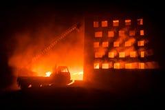 Потушите огонь частного дома на ноче Забавляйтесь пожарная машина с длинной лестницей и горящее здание на ноче Концепция пожарной стоковые фото