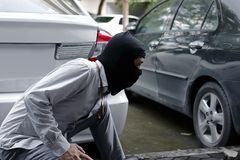 Похититель в черной балаклаве пробуя сломать в автомобиль стоковая фотография rf