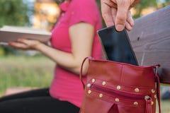 Похититель крадет smartphone от сумки женщины сидя на стенде Стоковое Изображение