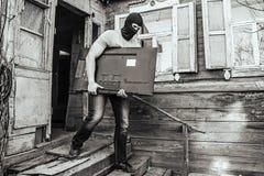 Похититель в маске облачённой дом стоковое фото rf