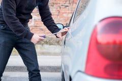 Похититель пробуя выбрать замок припаркованного автомобиля Стоковая Фотография