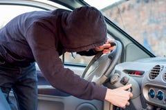 Похититель пробуя выбрать замок припаркованного автомобиля Стоковая Фотография RF